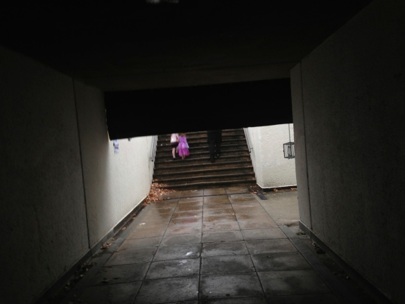 Looking out of the tunnel we see a little girl dressed as a princess from behind, climbing the stairs in the rain