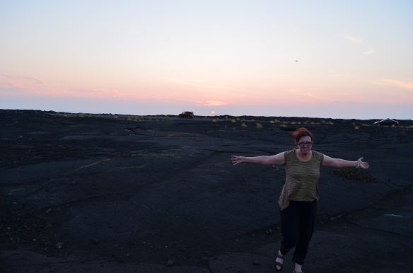 A photo of me running towards the camera on pitch black rocks, with the sun setting in the background