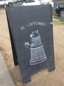 a chalk drawing of a dalek saying recaffeinate outside a cafe