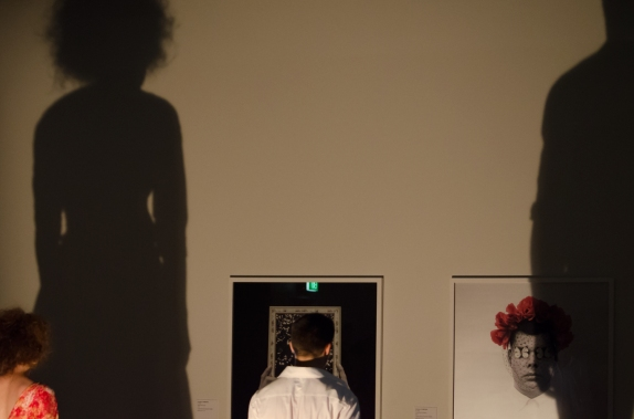 The woman and man's shadows are tall against the wall and cast across images on the gallery wall of a man and mirror with water in its frame
