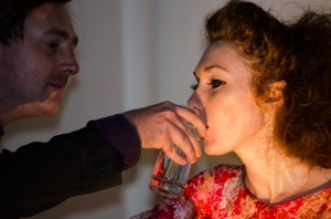 A man holds a glass of water for her to drink water, and she drinks