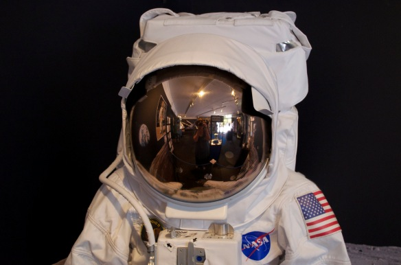 A picture of a a space suit with the authors reflection in the face shield, taking the photo