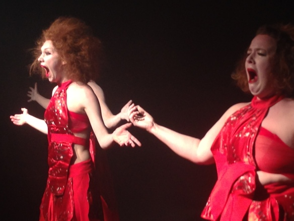 Three women in red arms raised in similar pose - screaming